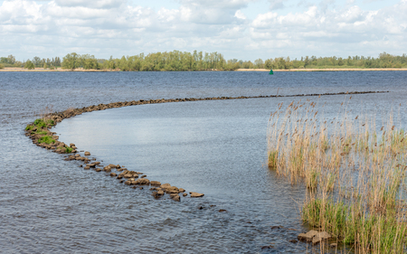 Curved dam of basalt boulders in the water of a Dutch river.