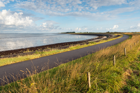 Curved asphalt road on a dike along the water of a Dutch estuary. It is low tide on a sunny day in the summer season. Imagens