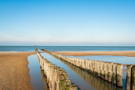 Breakwater made of a double row of wooden poles at the North Sea beach of the Dutch former island Walcheren. The poles are reflected in the mirror smooth water surface. It is a sunny day in winter.