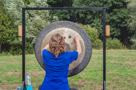 Unidentified young woman gives a demonstration with the rhythmical beating of a large gong in a Dutch park on a sunny day in the summer season. Stok Fotoğraf