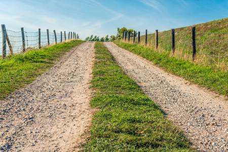 Tire tracks on a sandy driveway to the top of a Dutch dike. Beside the road are fences on both sides made of wooden poles and metal mesh. It is a beautiful sunny summer day today. Stockfoto - 108568558