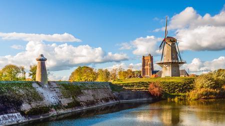 Kolorowy widok na panoramę holenderskiej twierdzy miasta Woudrichem w prowincji Brabancja Północna w słoneczny dzień w sezonie jesiennym. Na tym obrazie widoczne są jednocześnie trzy pomniki narodowe.