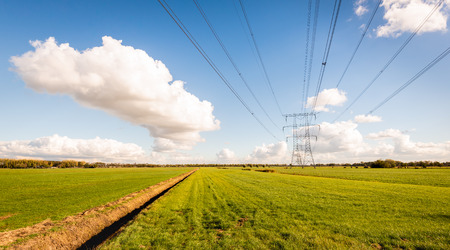 High voltage lines and power pylons in a Dutch agricultural landscape with large meadows. Diagonal in the image is a long ditch. It is a sunny day with a bright blue sky in the autumn season.