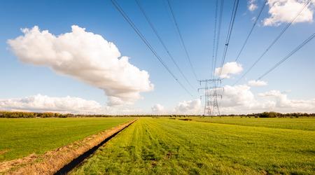 Hochspannungsleitungen und Strommasten in einer niederländischen Agrarlandschaft mit großen Wiesen. Diagonale im Bild ist ein langer Graben. Es ist ein sonniger Tag mit strahlend blauem Himmel in der Herbstsaison.