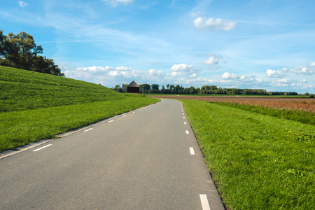 Curved country road next to a dike in a Dutch polder. The photo is made at the village of Hank, North Brabant. A restored reed worker's hut is visible in the background.