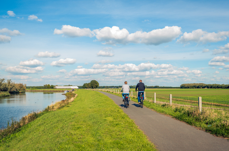 Two unidentified people cycle on a cycle path at the top of a dike along a narrow river at the Dutch National Park De Biesbosch in the province of Noord-Brabant. Stockfoto - 114465421