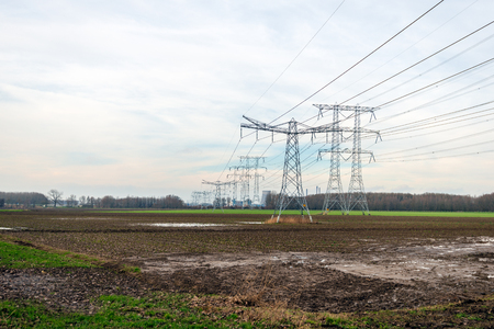 High-voltage pylons and high-voltage lines for transporting electricity from the power plant in the background. The photo was made close to Oosterhout in the Dutch province of Noord-Brabant. Stock Photo