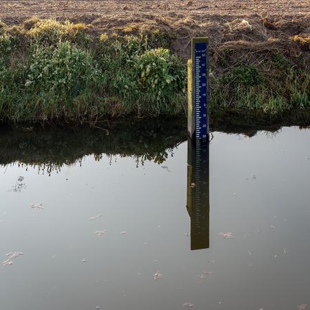 Misuratore di livello dell'acqua di colore blu e bianco in un fosso olandese riflesso nella superficie liscia dell'acqua a specchio. Il misuratore indica il livello dell'acqua in relazione al Normal Amsterdam Level (NAP). Archivio Fotografico