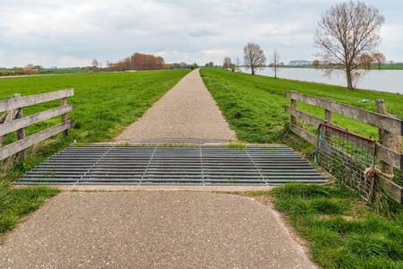 Cattle grid in a narrow cycle and walking path along a river in the Netherlands. The photo was taken near the village of Dussen and the river Bergsche Maas, North Brabant.