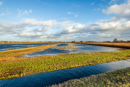 Blue sky with clouds reflected in the water of a flooded part of a Dutch polder. It is at the end of a sunny and windy day in the Zonzeelse Polder, North Brabant. Stockfoto - 124903543