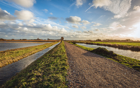 Apparently endless country road covered with colorful crushed stones. Water streams are on either side of the polder road. The photo was taken in the Netherlands at the end of the winter season. Stockfoto