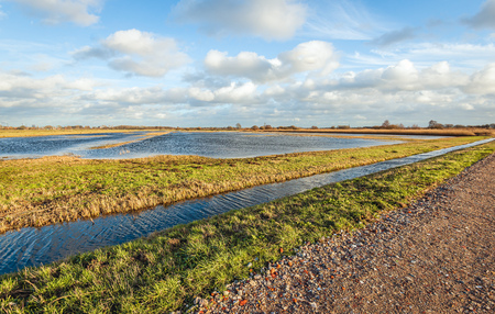 Ccountry road covered with colorful crushed stones next to a water stream with a riplled water surface. The photo was taken in the Zonzeelse Polder in the Netherlands at the end of the winter season. Stockfoto