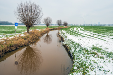 Dutch rural landscape in wintertime. The photo was taken near the village of Drimmelen, North Brabant. Along the Breede Vaart creek is a narrow bicycle path and a row of trees reflected in the water. Stockfoto - 124903547