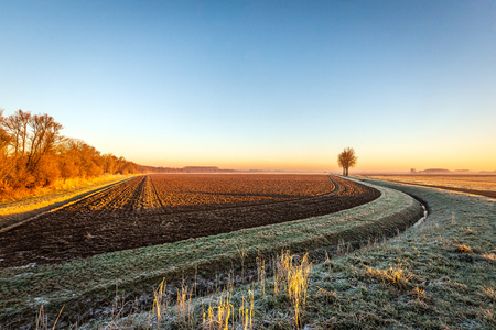 Plowed field next to a curved ditch in low sunlight in the winter season. The photo was taken in a Dutch polder near the village of Hank, North Brabant. It was early in the morning.