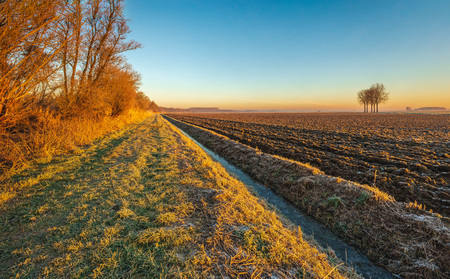 Plowed field next to a long and straight ditch in low sunlight in the winter season. The photo was taken in a Dutch polder near the village of Hank, North Brabant. It was early in the morning. Archivio Fotografico - 124903600
