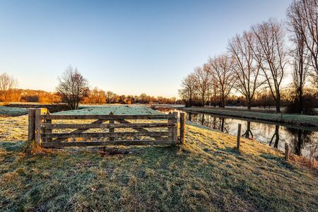 Wooden gate in a Dutch landscape with frozen grass. To the right is a row of bare tall trees reflected in the water surface of the river. The photo was taken in the Markdal, near the city of Breda.