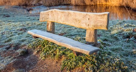 Rough wooden bench in the early morning sun. It is winter and the seat of the bench is covered in frost. Archivio Fotografico - 124903652