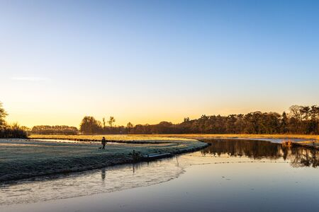 Dutch river Mark early in the morning on a sunny and windless day in the winter season. An unknown woman walks her dog. Stockfoto