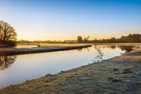Curve in the Dutch river Mark on a windless day in winter. The photo was taken on a sunny day early in the morning in the Markdal a nature reserve south of the city of Breda, North Brabant. Stockfoto