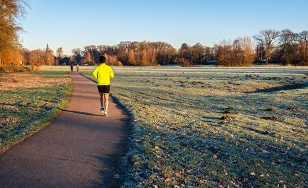 Woman in sportswear runs across a path in the park. It is early in the morning of a sunny day in the winter season. The photo was taken in nature reserve Markdal near the city of Breda, North Brabant.