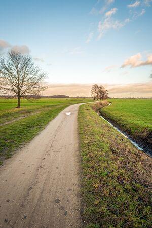 Curved sand path in a Dutch polder landscape in the winter season. The photo was taken in the Binnenpolder near the village of Terheijden, North Brabant. Archivio Fotografico - 124903664