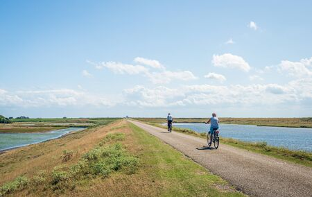 Unidentified cyclists on a Dutch dike on a sunny day in the summer season. The photo was taken near the village of Kerkwerve, Schouwen-Duiveland, Zeeland. On both sides of the dike are nature reserves