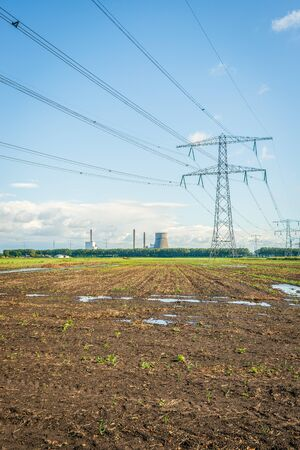 Converging high voltage lines and power pylons in a Dutch rural landscape. In the background the cooling tower and chimneys of a power station. It is autumn now and the field in the foreground is wet. Stock fotó - 132035672