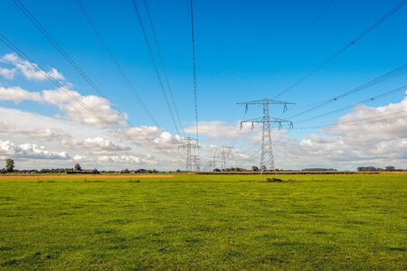 Converging high voltage lines and power pylons in a Dutch rural landscape. In the background is the edge of a small village in the province of North Brabant with some houses and farms. It is fall now. Stock fotó - 132035887