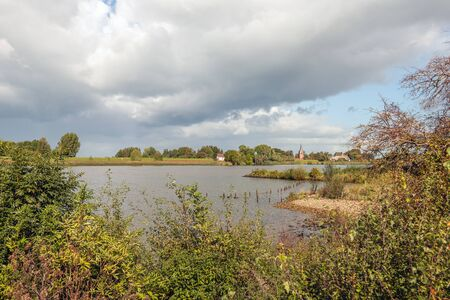 Bank of the Dutch river Lek near the village of Lexmond, province of South Holland. On the other side is Lopik, province of Utrecht. Dark clouds are hanging above the river