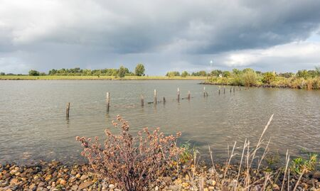 High water level in the wide Dutch river Lek. The photo was taken on a very cloudy day in the autumn season near the village of Lexmond,South Holland. The fence is largely flooded. Stockfoto