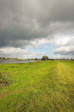 Vertical image of menacing dark clouds above the banks and the wide Dutch river Lek. It is a very cloudy day in the fall season. Shortly after taking this photo there was a heavy rain shower.