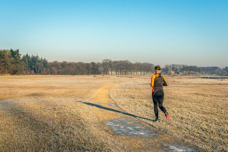 Unidentified female jogger runs across the grass. It is early in the morning on a sunny winters day. The grass is covered with hoarfrost. The photo was taken in the Markdal, a Dutch nature reserve.