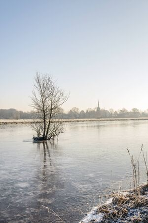Leafless branches in the foreground of the frozen Dutch river Mark. In the background is the edge of the small village Ulvenhout. It is still early in the morning of a beautiful day in the Dutch winter season. Stockfoto