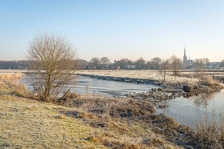 The outskirts of the Dutch village of Ulvenhout as seen from the Markdal nature reserve in Breda. North Brabant. It is winter and a thin layer of ice covers the water surface of the stream.