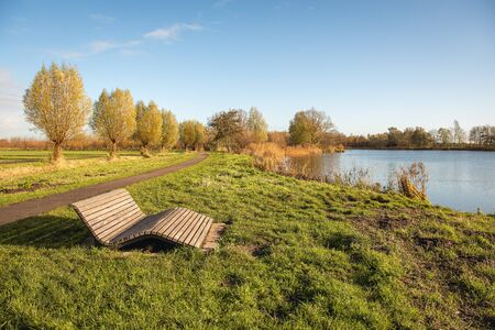 Elegantly designed wooden slat bench in a sunny location in a nature reserve on the edge of a lake. It is autumn in the Netherlands and the leaves on the trees are already discolored.