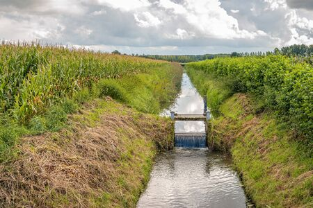 Backlight image of a small weir in a ditch between two fields in the Netherlands. At the weir there is a gauge to measure the water level. Stock Photo