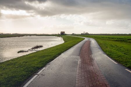 Meandering country road on a cloudy day in the Dutch fall season. The road, situated on a dyke, leads to a modern farm on a mound in the partially flooded Noordwaard polder in North Brabant.