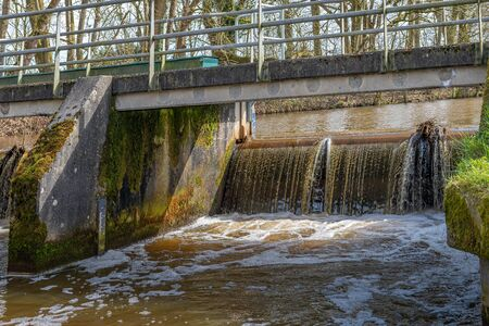 Water in a narrow Dutch river flows over the weir under the bridge. There is a water level meter on both sides of the weir on the wall.