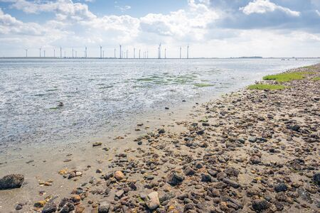 Dutch Krammer wind farm as seen from the stone-studded coast on the other side of the water. It is a sunny day in the summer season.