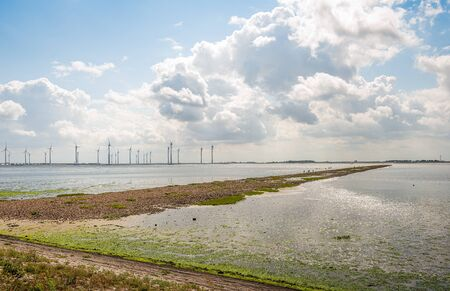 Dutch Krammer wind farm on the other side of the water. It is a sunny day in the summer season. There are clouds in the clear blue sky.