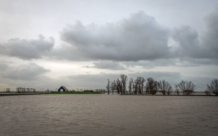 House on a mound in the flooded Dutch Noordwaard. Due to the high water level in the river Upper Merwede, the polder was flooded according in order to temporarily collect part of the surplus water.
