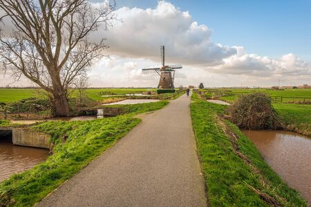 Country road with a lonely cyclist and mill in the Dutch polder near the village of Streefkerk, Alblasserwaard, South-Holland. Is is a sunny and cloudu day in the winter season.