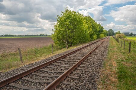 Picturesque landscape with seemingly endless long diagonal rusty single track rails. The photo was taken on a cloudy day in the Dutch spring season. Stockfoto