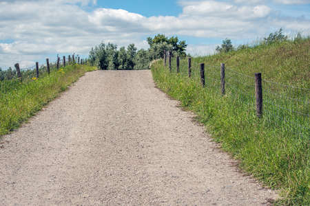 Sandy path with gravel as a driveway to the dike. On either side is flowering grass and wildflowers and a fence of wooden posts and wire mesh. The photo was taken on a sunny day in the Netherlands. Stockfoto