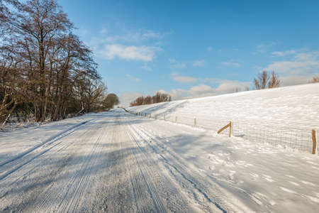 Apparently endless long road at the foot of a Dutch dyke. It is winter and a thick layer of snow has fallen. Tire tracks are visible on the road and paw prints of wild animals are visible on the verge.