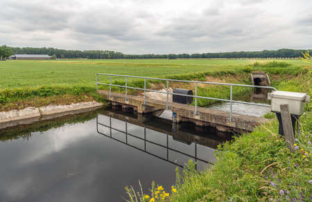 The water foams at the other site of the overflowing weir in a Dutch polder landscape. The small weird keeps the water at the right level in the agricultural polder area. Standard-Bild
