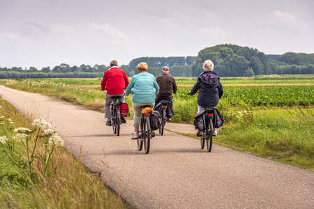 Two elderly unidentified couples with e-bikes cycle on a Dutch country road between fields in the province of North Brabant. The photo was taken on a slightly cloudy day in the summer season.