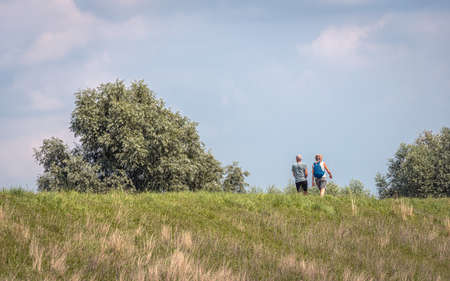 Man and woman walking on top of a Dutch dike on a sunny day in the summer season.