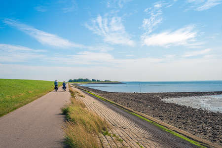 A man and a woman are cycling on a path at the bottom of a Dutch dike and along the Oosterschelde. The dike is reinforced with stones and partly covered with green algae. It's summertime now.