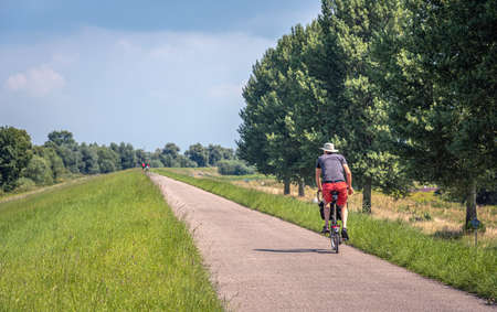 Man in shorts and hat cycles alone on a Dutch dike. It's a sunny day in the summer season. The photo was taken in the province of North Brabant.